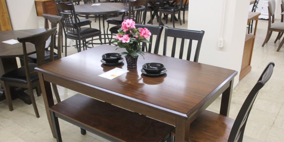 attractive dark hardwood dining room table with chairs, benches and glossy black vase and bowls