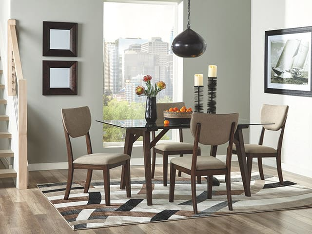 An Ashley dining room set, with area rug, framed pictures and accessories such as a vase and candles